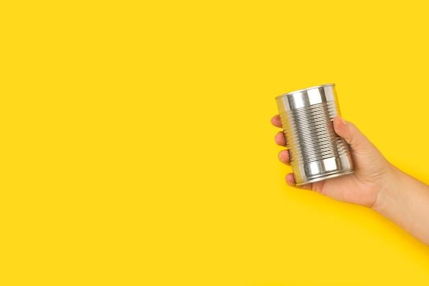 Mão de uma mulher segurando uma lata com espaço de cópia