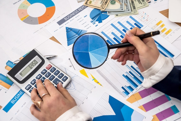 Mão de uma mulher segurando uma lupa sobre o gráfico de negócios