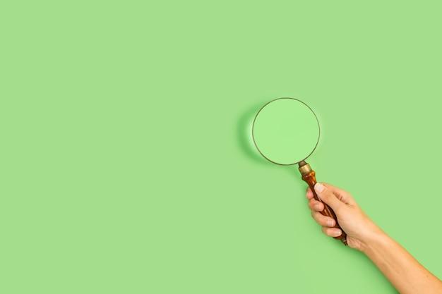 Mão de uma mulher segurando uma lupa sobre um fundo verde com espaço de cópia