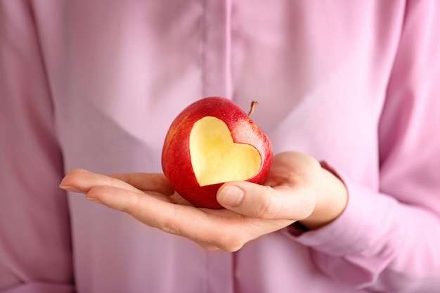 Mão de uma mulher segurando uma maçã vermelha fresca com recorte em forma de coração, close-up