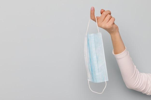 Mão de uma mulher segurando uma máscara médica facial no dedo, proteção contra vírus - covid-19 e coronavírus.