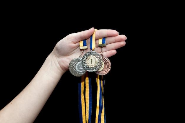 Mão de uma mulher segurando uma medalha de ouro, prata e bronze
