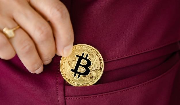 Mão de uma mulher segurando uma moeda criptográfica e colocando no bolso. conceito de investimento em ativos digitais e criptomoeda.