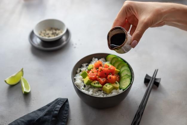 Mão de uma mulher segurando uma panela com molho de soja para polvilhar uma tigela de puxão havaiano com salmão, arroz, abacate e pepino. comida asiática tradicional.