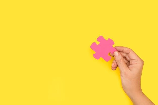 Mão de uma mulher segurando uma peça rosa do quebra-cabeça