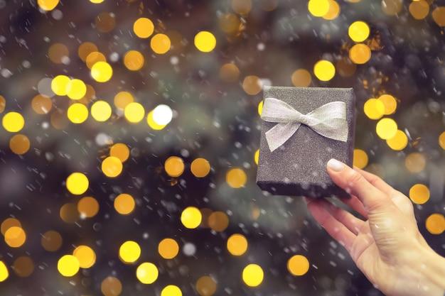 Mão de uma mulher segurando uma pequena caixa de presente de prata com um laço no fundo da árvore de natal durante a queda de neve. espaço vazio