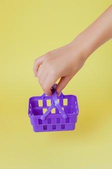 Mão de uma mulher segurando uma pequena cesta de compras