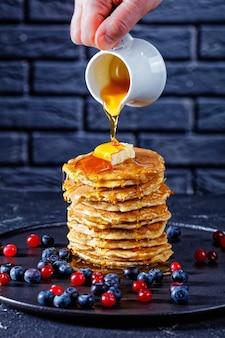 Mão de uma mulher segurando uma pequena jarra e derramando mel derretido em uma pilha de panquecas cobertas com um pedaço de manteiga servido
