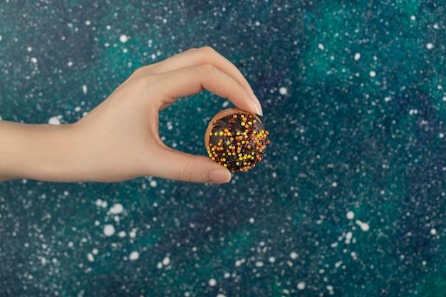 Mão de uma mulher segurando uma pequena rosquinha de chocolate.