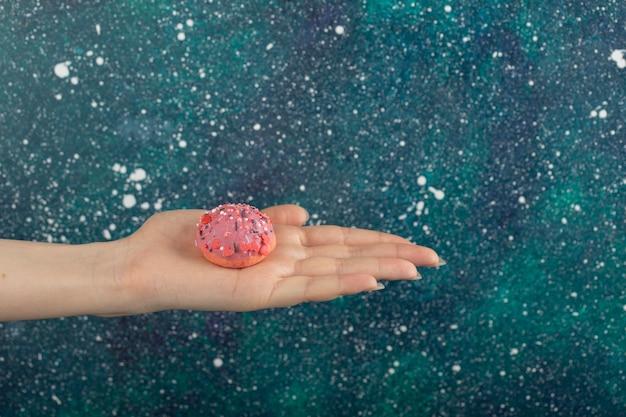 Mão de uma mulher segurando uma pequena rosquinha rosa.