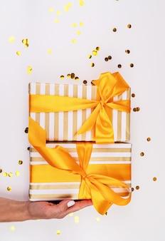 Mão de uma mulher segurando uma pilha de presentes brancos e dourados com confetes espalhados