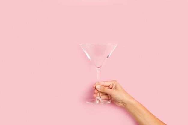 Mão de uma mulher segurando uma taça de coquetel em um fundo rosa