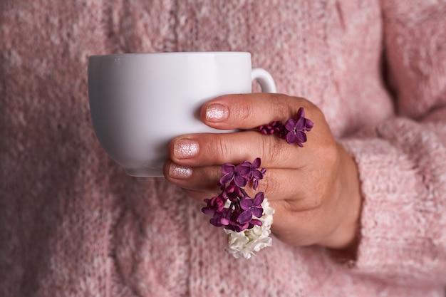 Mão de uma mulher segurando uma xícara de café branca. com uma linda flor lilás. bebida, moda, manhã