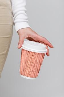 Mão de uma mulher segurando uma xícara de café de papel rosa com tampa de plástico branca