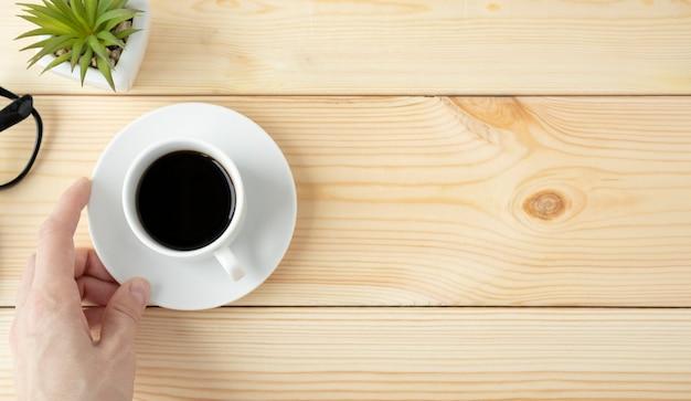 Mão de uma mulher segurando uma xícara de café quente em uma mesa de madeira com uma plantinha em uma panela