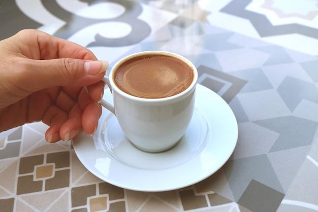 Mão de uma mulher segurando uma xícara de café turco, servido em uma mesa mourisca