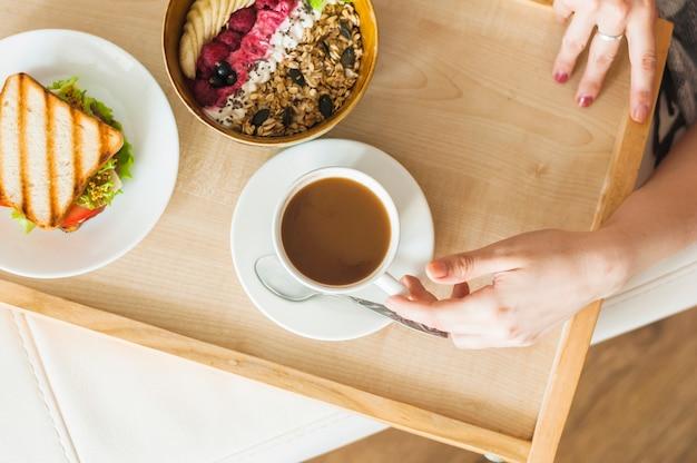 Mão de uma mulher segurando uma xícara de chá com café da manhã saudável na bandeja de madeira