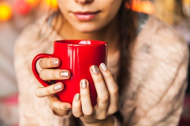 Mão de uma mulher segurando uma xícara vermelha de café. com uma bela manicure de inverno. bebida, moda, manhã