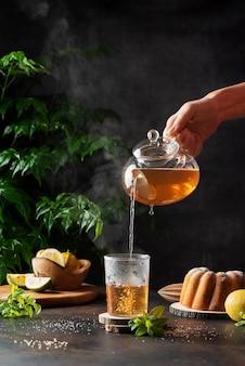 Mão de uma mulher servindo chá preto quente no fundo preto, imagem de foco seletivo