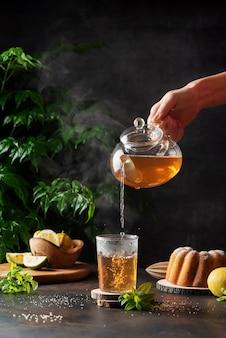 Mão de uma mulher servindo chá preto quente no fundo preto