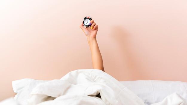Mão de uma mulher subindo um relógio debaixo de lençóis