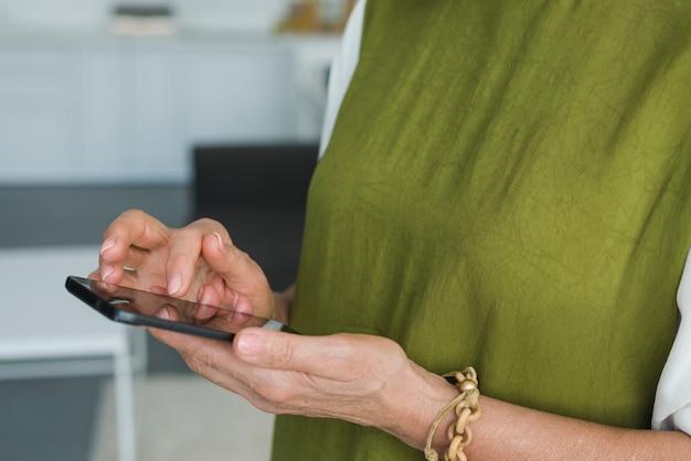 Mão de uma mulher tocando a tela do smartphone