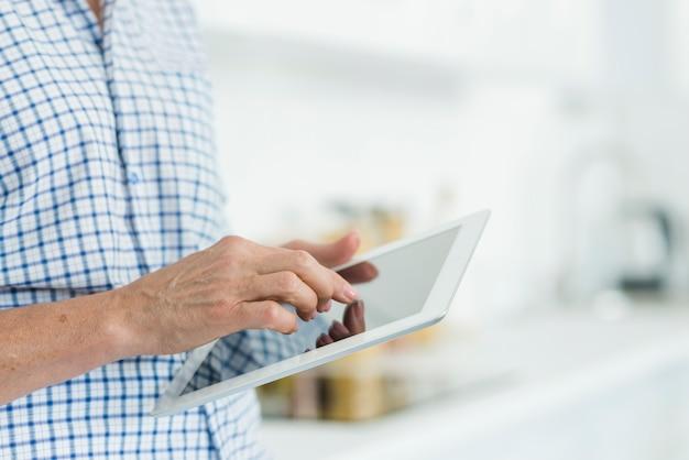 Mão de uma mulher tocando a tela do tablet digital