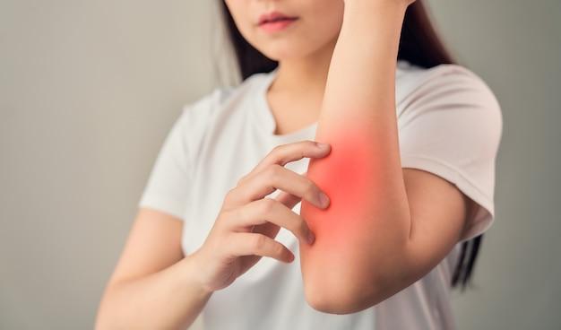 Mão de uma mulher tocando o cotovelo do reumatismo articular crônico e há muito sofrimento. sobre o fundo cinza.