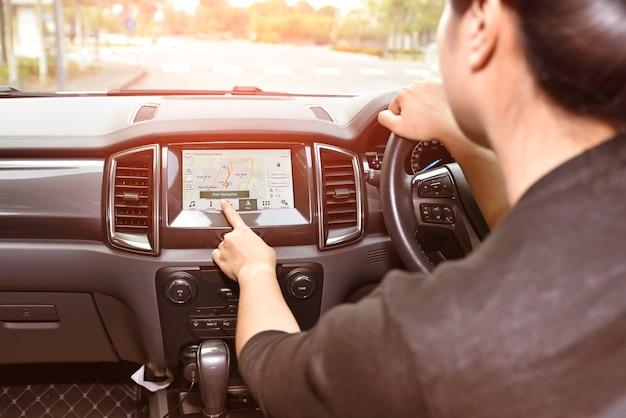 Mão de uma mulher tocando o sistema multimídia de tela com o aplicativo de navegação gps.