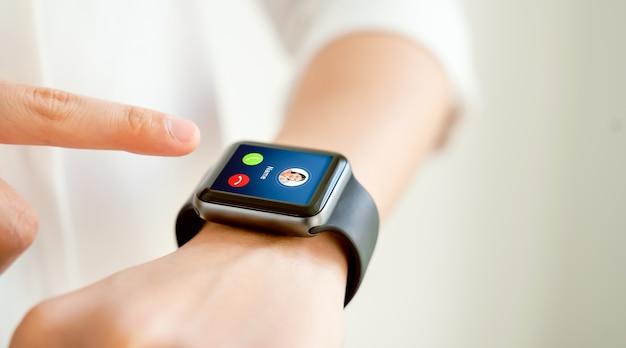 Mão de uma mulher tocando o smartwatch para desbloquear e mostrar a tela de chamada com o amigo.