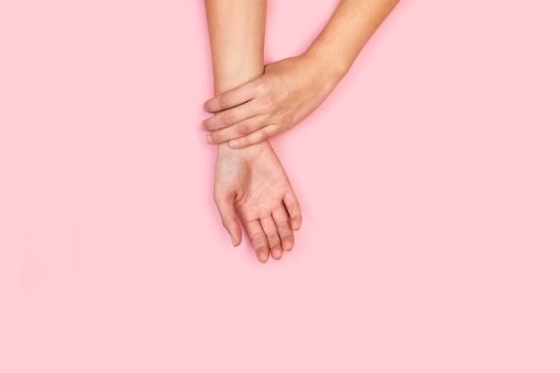Mão de uma mulher tocando seu próprio pulso em um fundo rosa em uma vista superior