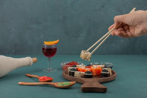 Mão de uma mulher tomando sushi com pauzinhos e uma taça de vinho.