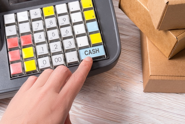 Mão de uma mulher trabalhando com caixa registradora eletrônica