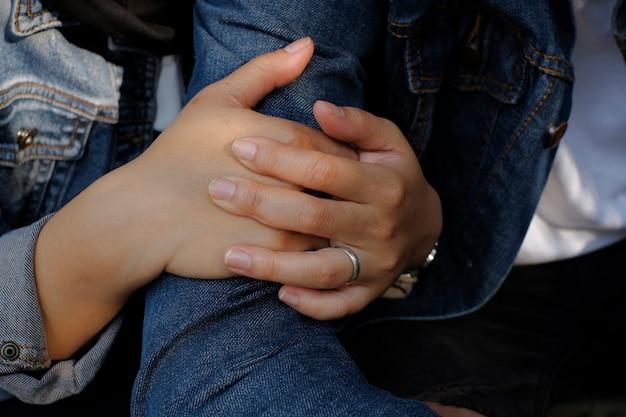 Mão de uma mulher usando anel e abraçando o homem