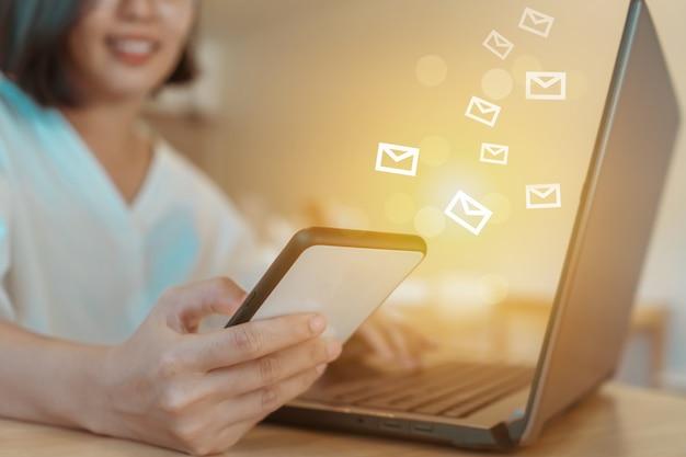 Mão de uma mulher usando o computador portátil para enviar e receber e-mail para negócios.