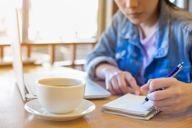 Mão de uma mulher usando o laptop e escrevendo no bloco de notas.