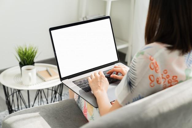 Mão de uma mulher usando o laptop na mesa em casa, mock-se da tela em branco.