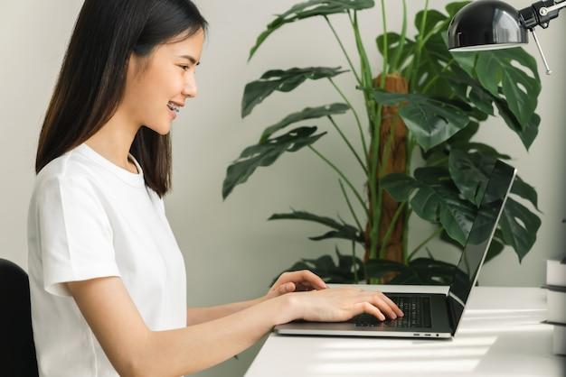 Mão de uma mulher usando o laptop na mesa em casa, simulação de tela em branco.