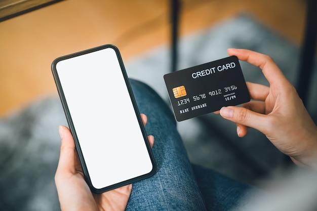Mão de uma mulher usando smartphone e segurando o cartão de crédito com pagamento online no celular.