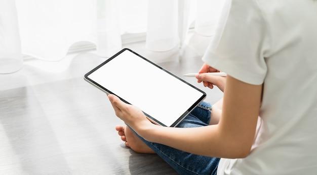 Mão de uma mulher usando tablet digital e a tela está em branco.