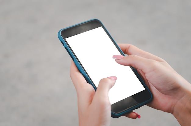 Mão de uma mulher usando um telefone celular simulado uma tela em branco.