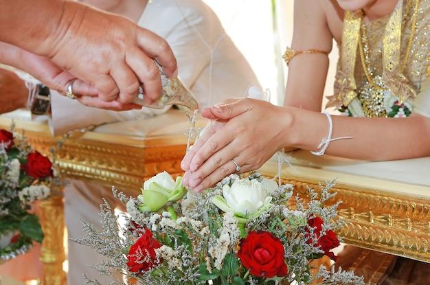 Mão de uma noiva, recebendo água benta de anciãos na cerimônia de casamento de cultura tailandesa