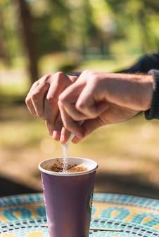 Mão de uma pessoa, adicionando o açúcar na taça de café fora levar ao ar livre