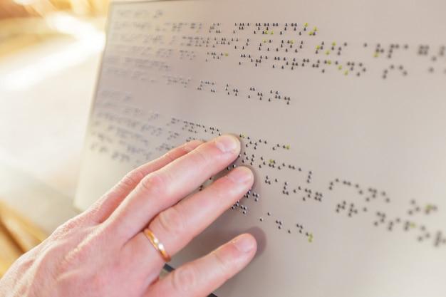 Mão de uma pessoa cega que lê algum texto do braile que toca no relevo.