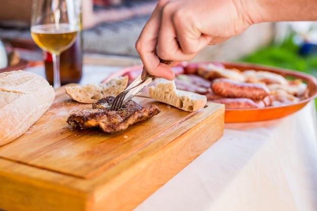 Mão de uma pessoa cortar carne cozida na tábua de cortar