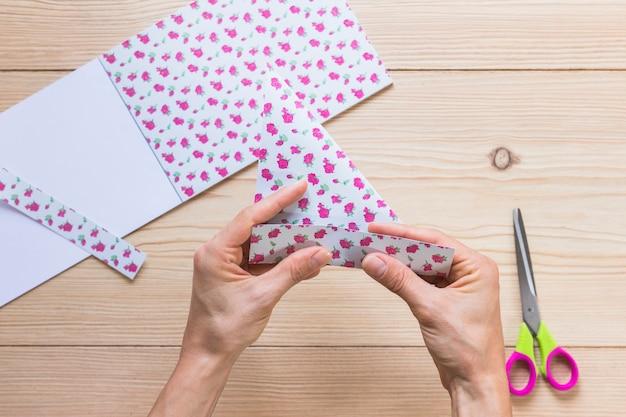 Mão de uma pessoa, dobrando o papel de scrapbook sobre a mesa