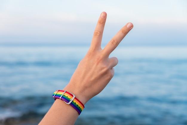 Mão de uma pessoa em uma pulseira colorida gesticulando o sinal v