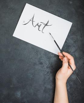Mão de uma pessoa escrita texto de arte com pincel na folha de papel