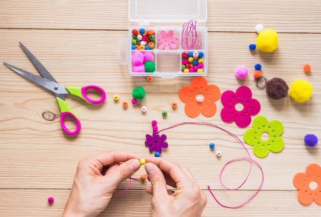 Mão de uma pessoa fazendo jóias artesanais com miçangas e patch de flor