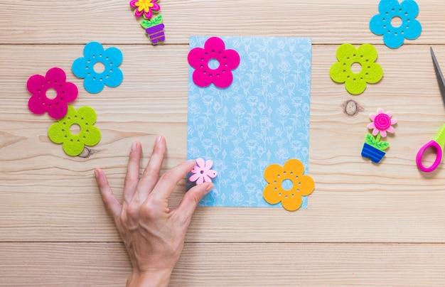 Mão de uma pessoa, furando o patch de flor no cartão de scrapbook